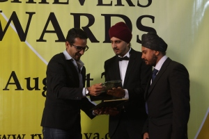L to R Gupz Saund receives his trophy for Best Music Vocalist from Angad Roopra & Himath Gahir