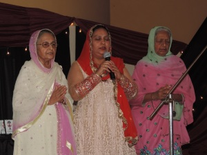 L to R Kuldeep Dogra, Amarjeet Kaur, Joginder Sehmi recite the Prayer to open the Celebrations